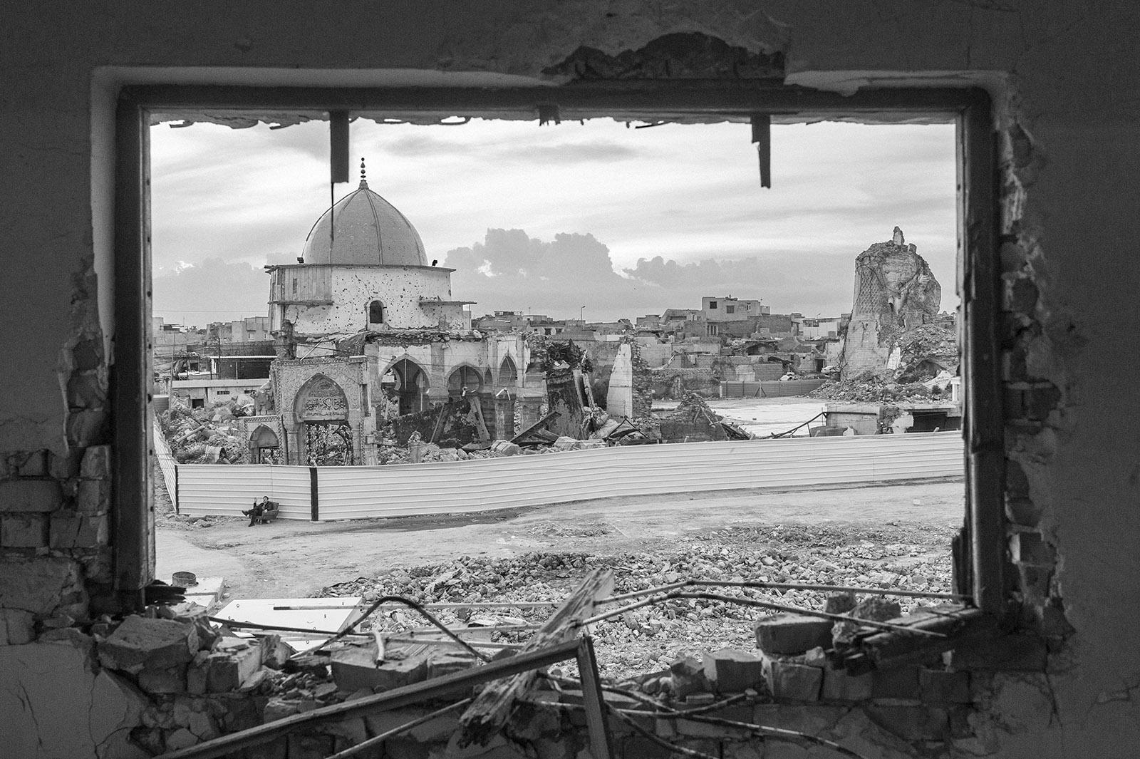 Milo Rau sitzt in der Altstadt von Mossul an der Al-Nuri Moschee. Mossul, Irak.